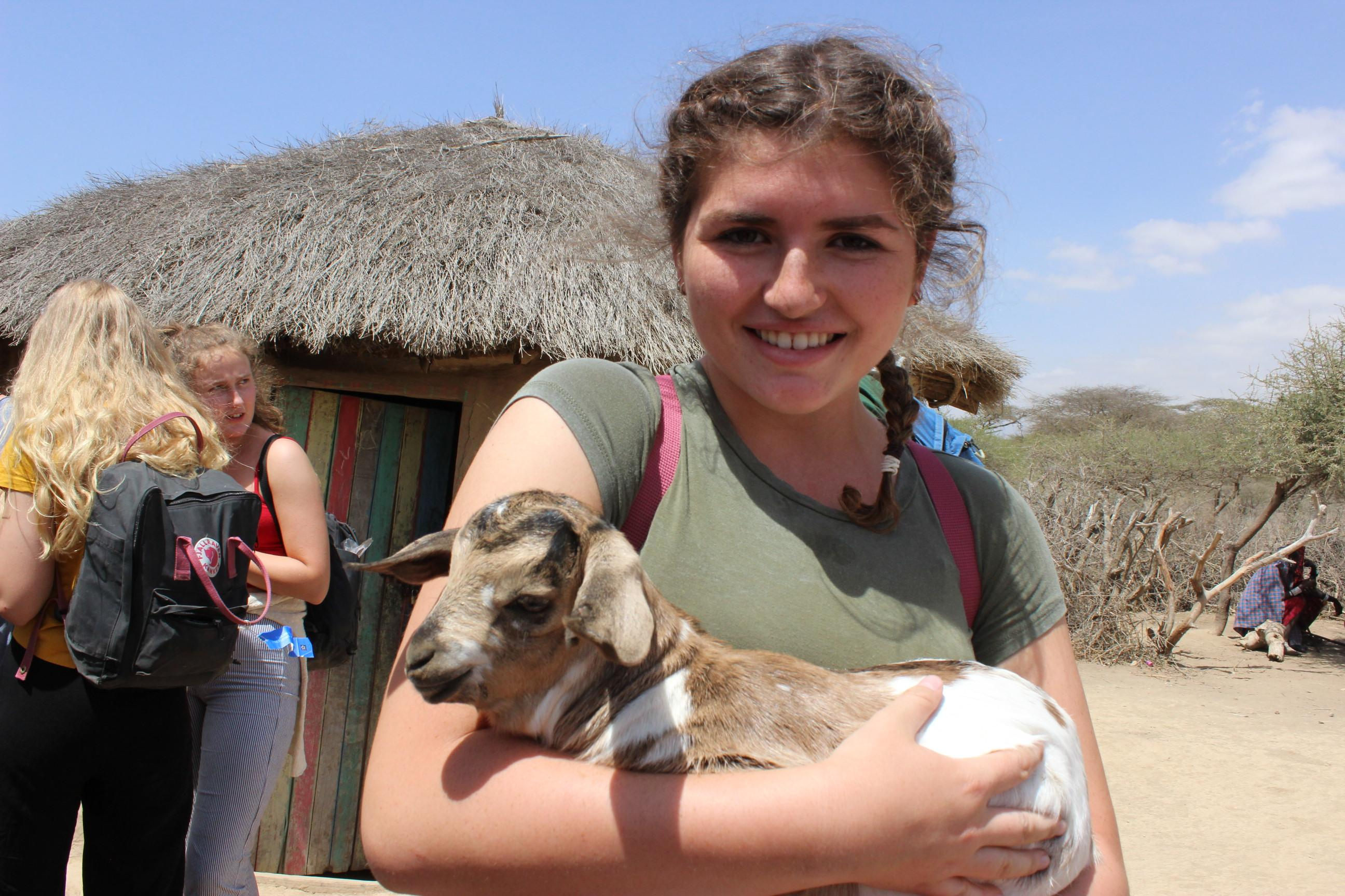 Young Female Community Volunteer poses for a photo holding a baby goat during her volunteering project in Tanzania.